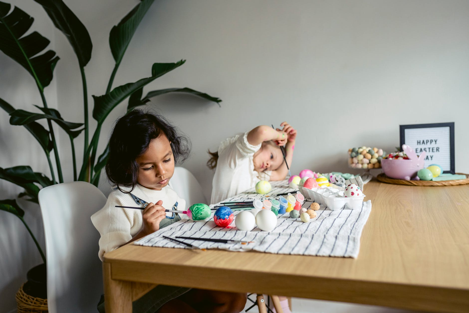 focused multiracial girls painting eggs at table